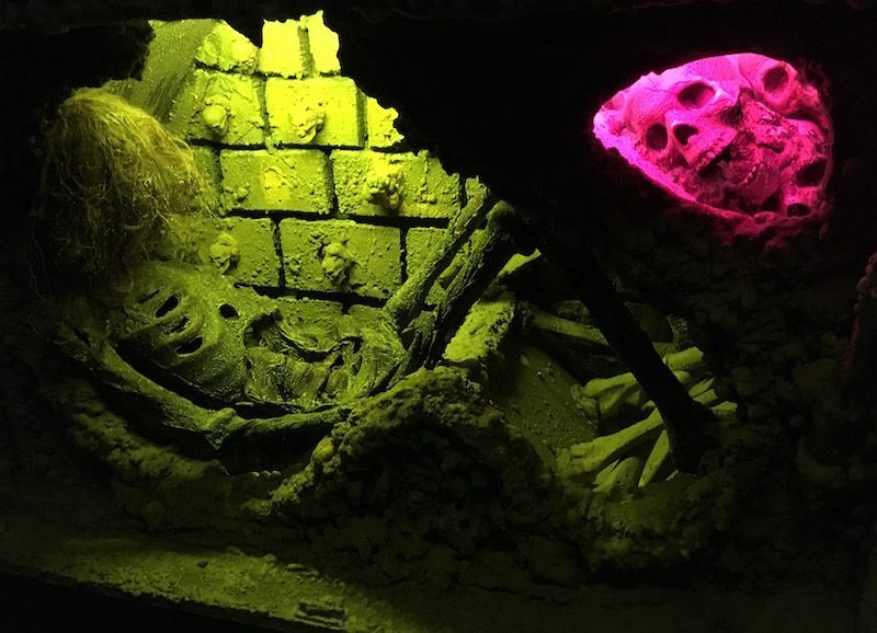 In-game: Two alcoves in a stone wall. One has a human skeleton in it, the other has multiple human skulls.