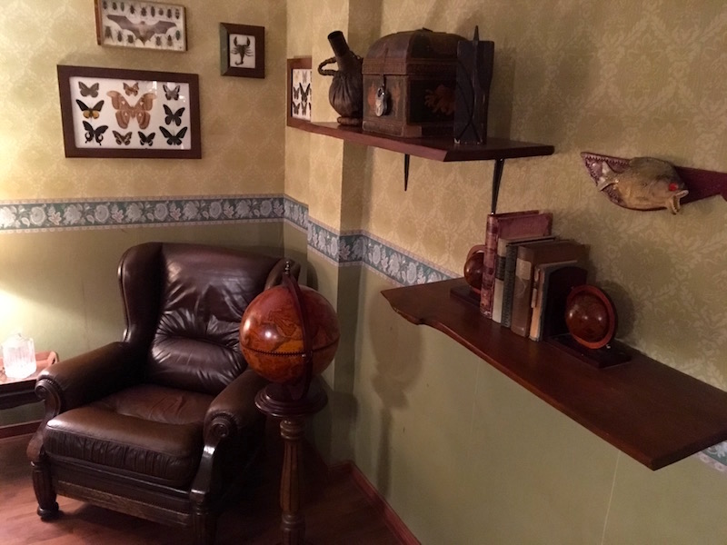 In game: A room corner with a large leather chair, a globe, and artifacts from around the world.