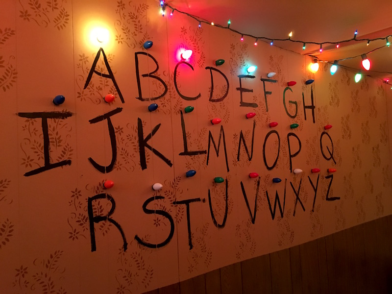 "In-game: The alphabet drawn on a wallpapered and wood paneled wall. Above each letter is a christmas light. ""ACE"" are illuminated."