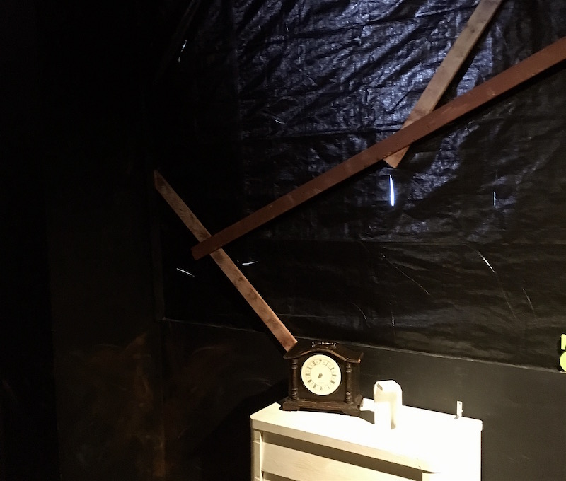 In-game: A wall covered in a torn black tarp and wood scrapes. A clock rests on a small white table.