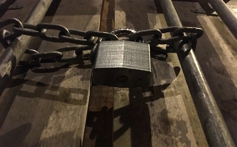 In-game: A close up an an intense barred door held shut by a chain and laminated padlock.
