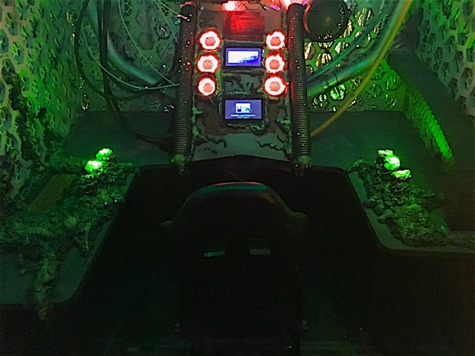 In-game: A cockpit glowing green with red accents. It looks like a mix of technology and biology.