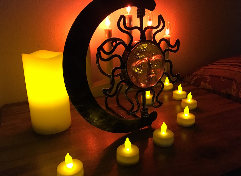 In-game: A close up of an array of LED candles surrounding a small statue of a sun.