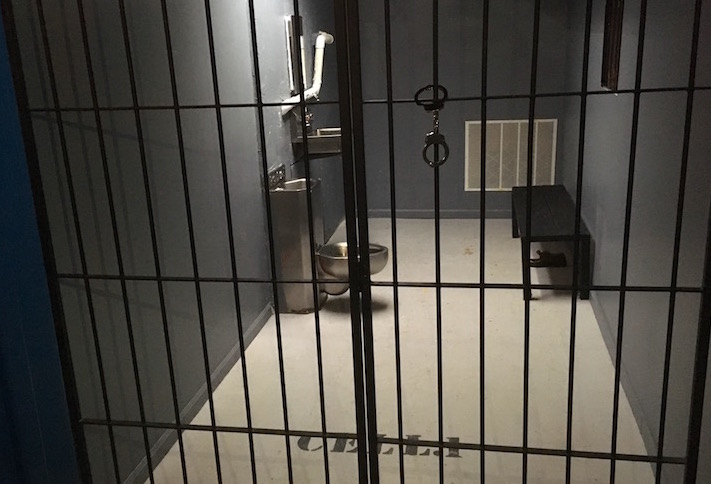 In game: A jail cell with a wooden bench and a metal toilet.