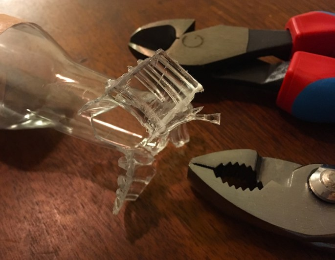 A plastic bottle with a mangled mouth. A pair of wirecutters and pliers sit beside it.
