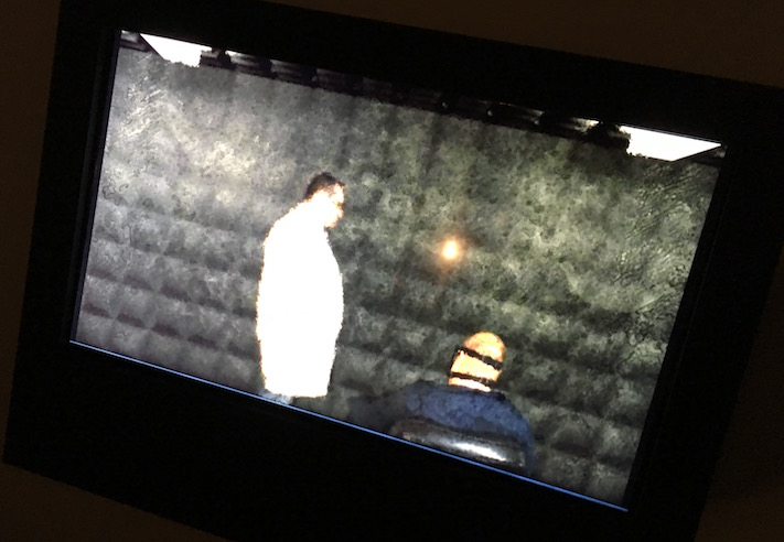 In-game: a TV depicting a doctor speaking with a restrained patient in a padded cell.