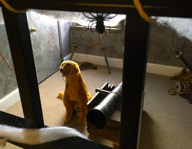 In game: Behind a jail gate, a dog with keys in his mouth sits beside a cannon.