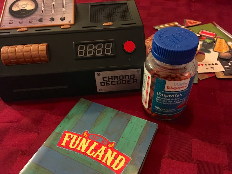 The chrono decoder, Funland cover, and game components along with a bottle of Ibuprofen.