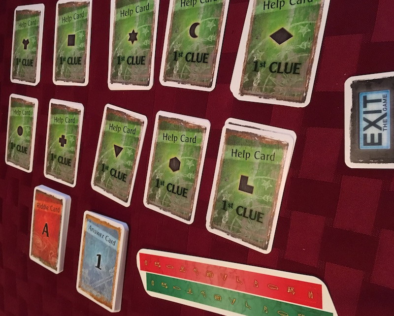 In-game: An assortment of hint cards organized by shape, riddle cards, and answer cards.