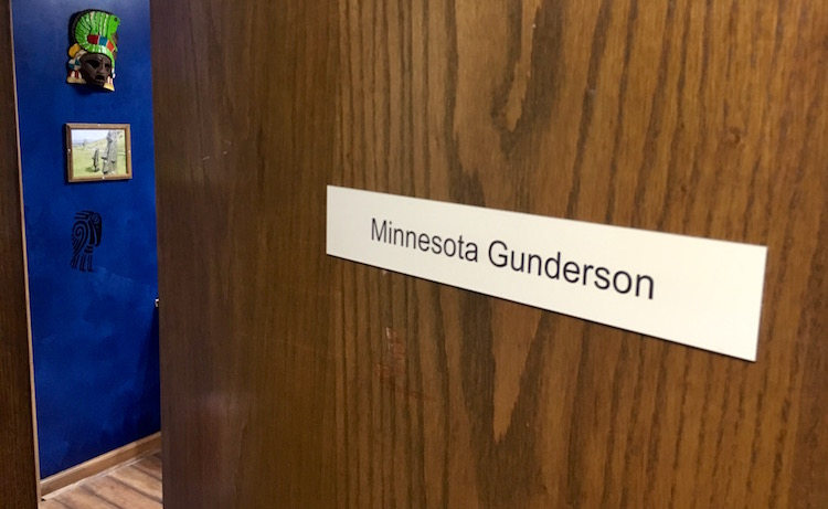 In-game: The cracked door of Minnesota Gunderson's office. His blue walled office with artifacts hanging on the wall are visible beyond the door.