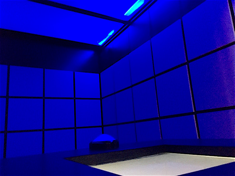 In-game: A futuristic, sci-fi-looking tiled room lit blue.