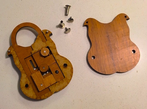 Sliding Lock puzzle with the screws and back removed. The intricate pieces are exposed and loose.