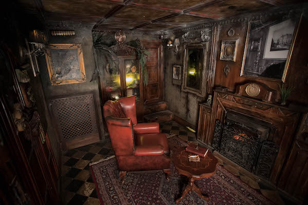 In-game: A wide shot of the living room set a large red chair in front of a fireplace in an old, rundown home.