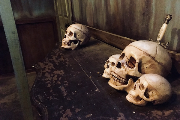 In-game: 4 skulls resting on a small table in an old rundown room. The largest skull has a knife protruding from it.