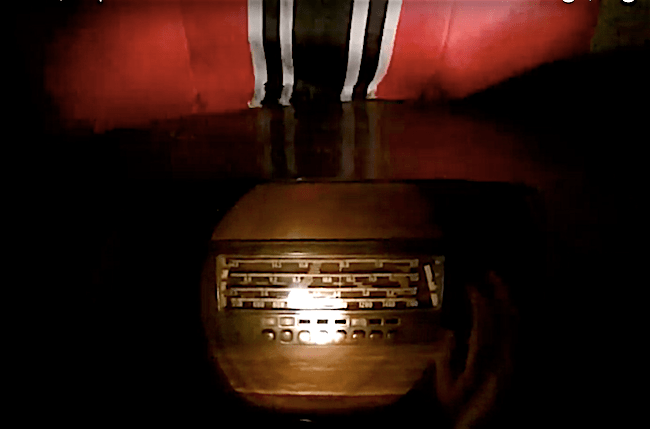 In-game: An old jukebox illuminated by flashlight. The bottom of a Nazi flag in the background.
