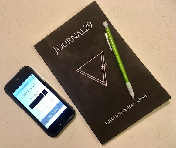 The Journal29 book, a pencil, and a iPhone with the Journal29 website open.
