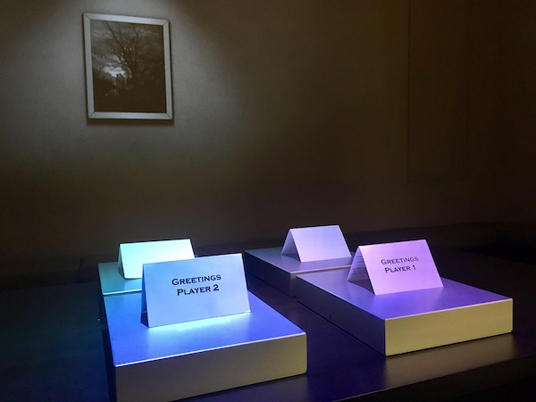 In-game: A dark room with featuring a table lit dramatically with 4 boxes, each with a card greeting a different player.