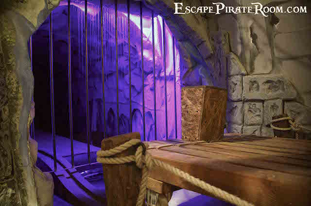 In-game: A wood raft in front of the gated entrance to a cave