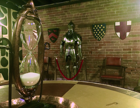 In-game: An ornate hourglass sitting on a table in the foreground. A suit of armor flanked by shields in the background.