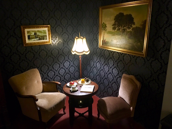 In-game: A dark and intricate study space with two large comfortable chairs beside a table with snacks and coffee.