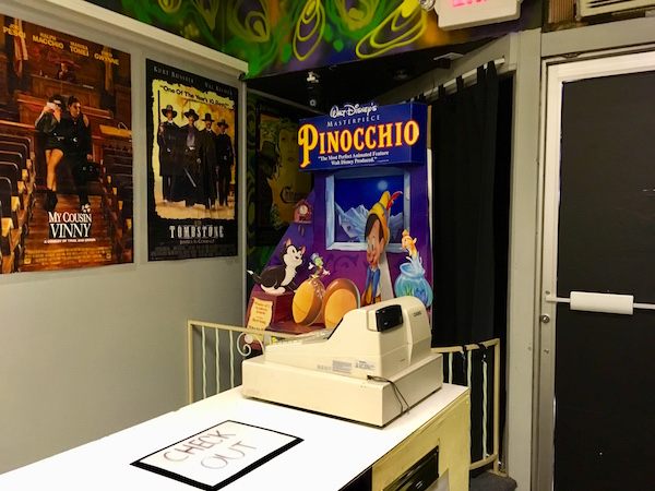 In-game: A cash register at the checkout station of the video rental. There is a big cardboard pop up for Pinocchio.