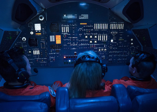 In-game: Three astronauts strapped into their seats with an intricate dashboard in front of them.