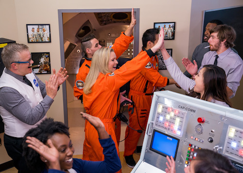 In-game: A team of astronauts and Mission Control high fiveing after a successful mission