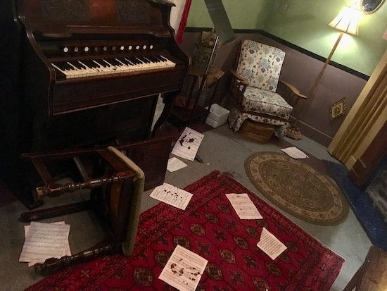 In-game: An organ covered in blood with bloodied sheet music strewn about a ransacked parlor.