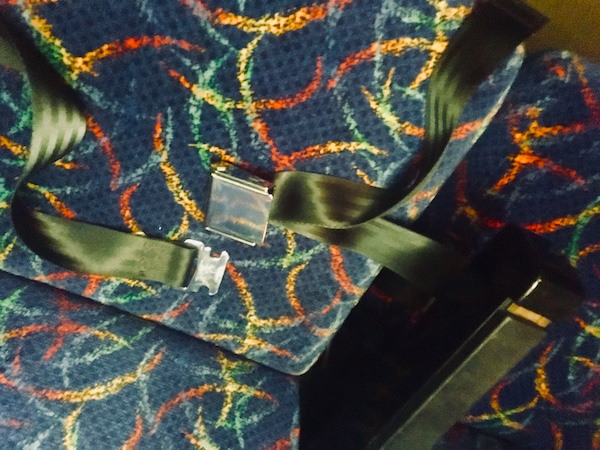 In-game: A close-up of a coach seat with the seat belt laying atop it unlatched.