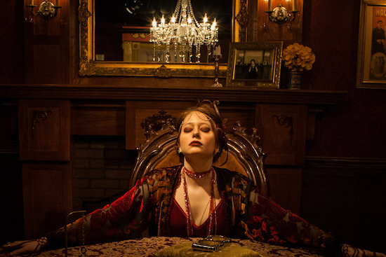 Madame Daphne, dramatically lit, sitting in a large chair at her seance table. Her arms out stretched and eyes closed.