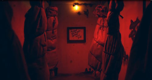 In-game: A room lit red with bodies wrapped up and hanging from the ceiling.