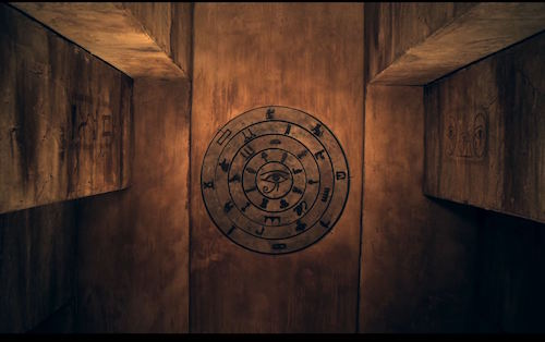 In-game: A narrow corridor in an Egyptian tomb with a circular series of wheels with symbols on the far wall.