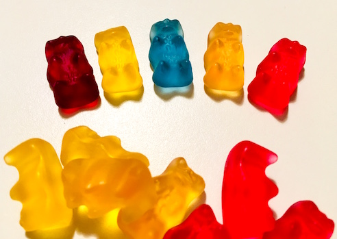 The 5 colors of gummy bears laid out. The orange and yellow bears are very similar.