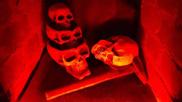 In-game: Skulls nested in one another beside a hammer within a fireplace.