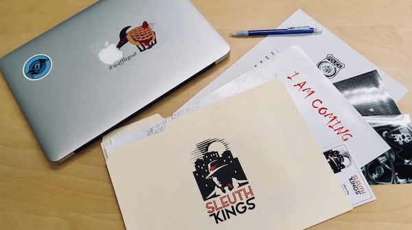 The Sleuth Kings folder of materials next to a laptop with the Room Escape Artist logo.