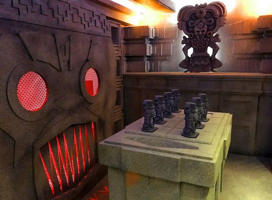 In-game: A stone alter with glowing red eyes and teeth and a pedestal with small statues atop it.