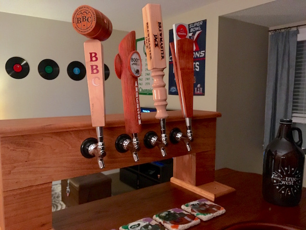 In-game: a bar with 4 beer taps and a growler in the middle of an apartment with walls covered in sports posters and vinyl records.