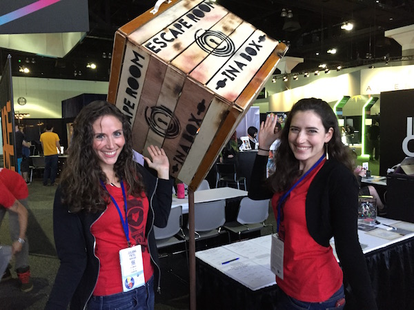 "Juliana & Ariel at a conference in front of an oversized wooden box labeled, ""Escape Room In A Box."""