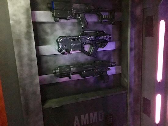 In-game: 3 futuristic guns hanging on the wall of a space ship.