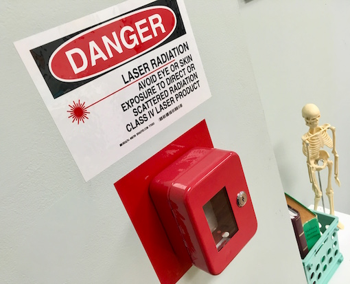 "In-game: A red box mounted to the wall and locked shut. Above it a sign reads, ""Danger: Laser radiation avoid eyes or skin."""