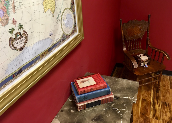In-game: A map mounted to the wall, a stack of books on a small table, and a arm chair with a locked box.