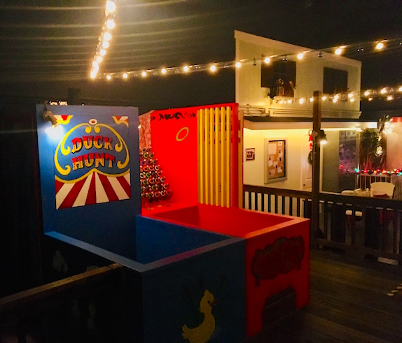 In-game: A duck hunt and ring toss carnival game on a boardwalk lit festively at night.