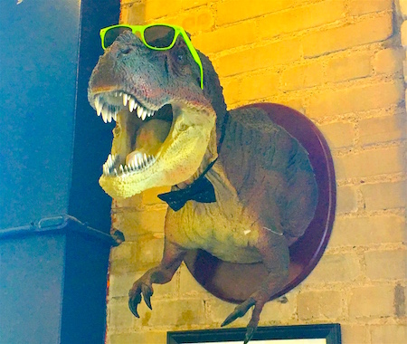 T-rex taxidermy in big green sunglasses and a bowtie.