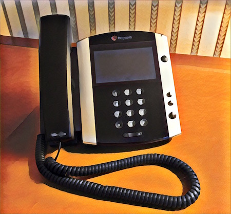 Vibrant filtered image of a Polycom telephone resting on a wood and leather desk.