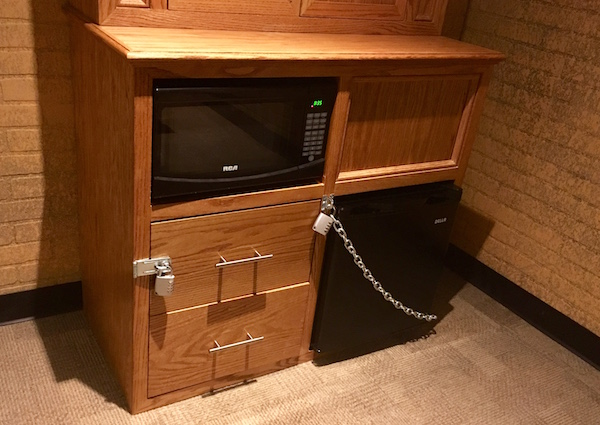 In-game: A seedy hotel mini-fridge, microwave, and dresser covered in padlocks.