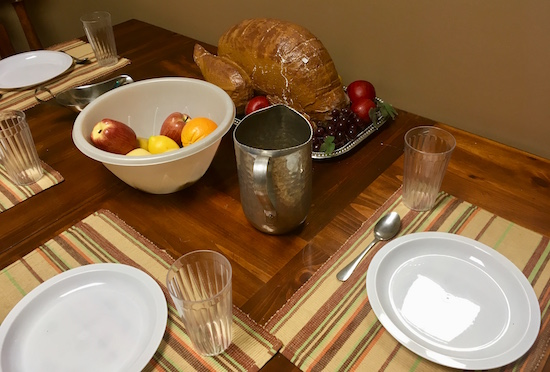 In-game: a set dining table with fruit and a turkey in the middle.