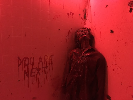 In-game: a dead body hung by a hook in his mouth hands next to a bloody message,