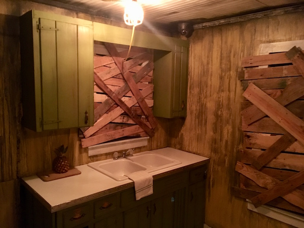 In-game: A rundown kitchen with boarded up windows.