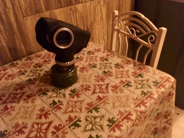In-game: a kitchen table with a gas mask resting atop.