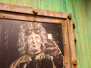 In-game: a portrait of a mad scientist framed with an oxidizing metal frame.
